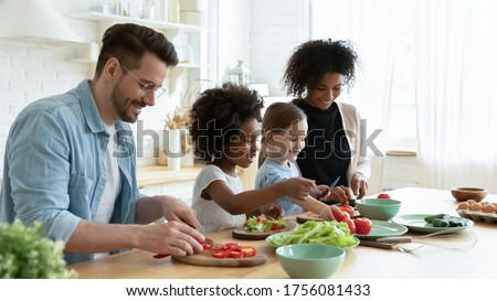 Full multinational family with cute daughters preparing dietary meal natural nutrition, cutting fresh vegetable for salad, parents caring for children health eat organic food, weekend activity at home