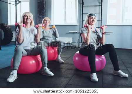 Full of energy and joy. Focused senior female friends smiling while taking an exercise class and training with dumbbells while sitting on fitness ball in a gym.