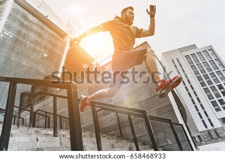 Full of energy. Full length of handsome young man in sport clothing jumping while exercising outside