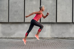 Full of energy. Side view of active middle aged woman in sport clothing jumping while exercising outdoors. Healthy lifestyle concept. Sport after 50