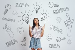 Full of ideas! Cute asian woman with long hair pointing up at pointing at drawn light bulbs above her head and smiling while standing against grey background with hand drawn doodles on it