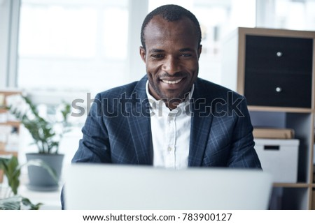 Full of joy. Portrait of optimistic young successful african businessman in suit is sitting at table in office and using modern laptop. He is looking at monitor with wide smile