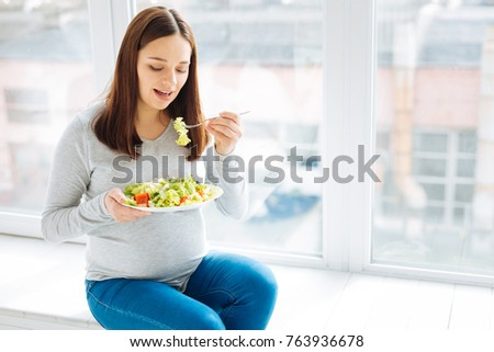 Full of vitamins. Energetic good looking pregnant woman eating her meat while carrying plate in a hand and relaxing against the window