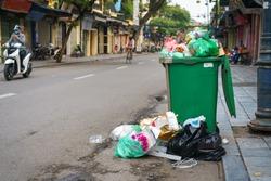 Full over capacity green dust bin on old town street in Hanoi, Vietnam