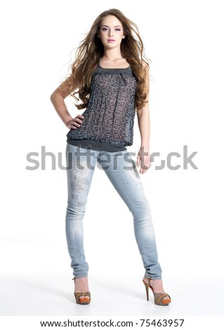 Full portrait of beautiful stylish girl in fashion stylish jeans posing - isolated on white background.  Fashion model posing at studio. Full length portrait