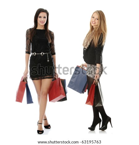 Full portrait of elegant two young women with shopping bags, isolated on white background