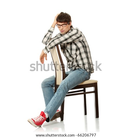 Full portrait of serious handsome man sitting on the chair, isolated on white