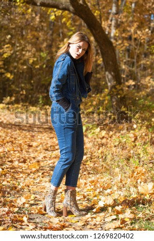 Full portrait of Stylish young blonde woman in blue denim overalls in autumn park
