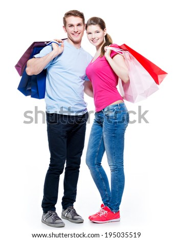 Full portrait of the happy young couple with shopping bags - isolated on white background.