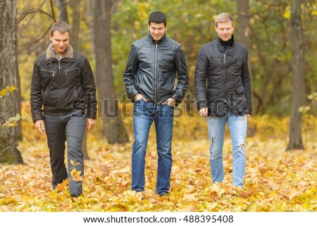 Full portrait of three friends walking in autumn park, under feet of yellow foliage #488395408