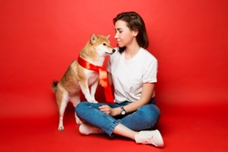 full portrait of young brunette woman in white t shirt, jeans and white sneakers sitting with a yellow white dog with red bow on  plain red background