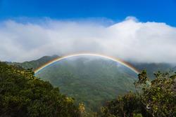 Full rainbow in the evening over a lush Hawaiian valley