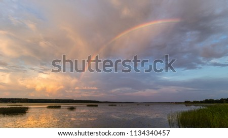 Stock Photo Full rainbow over the lake after a rainy summer evening. The sky shows beautiful clouds that are reflected in the water.