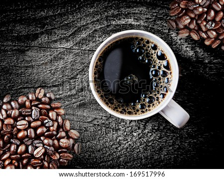 Full roast coffee beans piled on a rough rustic wooden surface with a cup of freshly brewed espresso coffee with frothy bubbles, close up overhead view