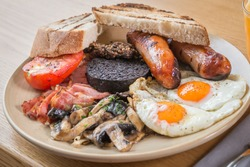 Full Scottish breakfast containing tomato, black pudding, haggis, sausages, bacon, mushrooms, fried eggs and toast.