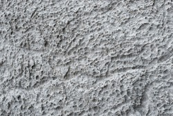 Full-screen texture of weathered and eroded gray limestone