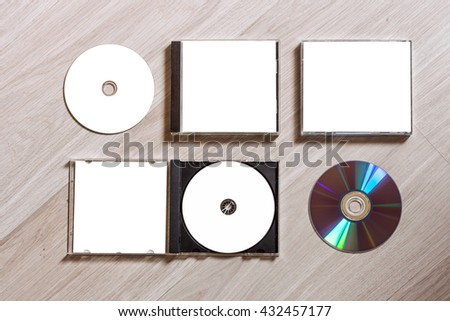 Full set compact disc template with plastic box case with white isolated blank for branding design and open box with booklet and back side. CD jewel case mock up with free space on wooden table.