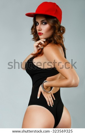 full sexy young girl in a black bathing suit and a red baseball cap sexy posing with a big booty