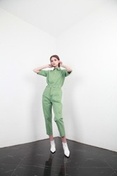 Full shot of a brown haired European lady with long hair in a summer cotton two piece suit, standing in a simple interior with white walls, studio photography, copy space