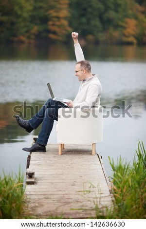 Full side view of excited mature man celebrating victory while using laptop on pier