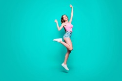 Full size body length of young slim magnificent sweet laughing girl in top and jeans shorts, sneakers, dancing in air, raising hands up, celebrating. Isolated over bright vivid turquoise background