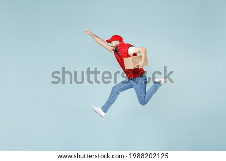 Full size body length side view delivery guy employee man in red cap white T-shirt vest uniform work as dealer courier jump run go walk isolated on pastel blue color background studio. Service concept