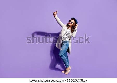 Full size body of happy smiling girl in jeans overcoat street look shooting self portrait on front camera of smart phone posing isolated on violet background