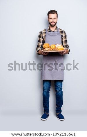 Full size body portrait of joyful cheerful baker in jeans, shoes, shirt, apron with stubble having, showing tray with bakery products, looking at camera, isolated on grey background #1092115661