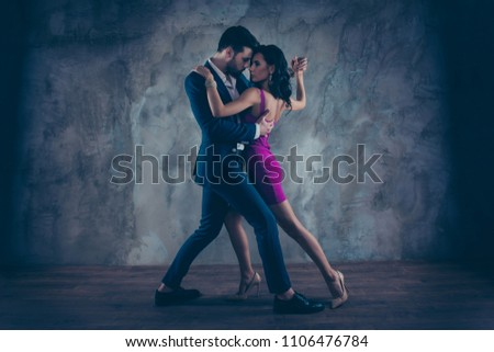 Full size body portrait of lovely attractive couple standing close in tango position face to face dancing, charming lady in purple tight dress gentlemen in tux isolated on grey background movement