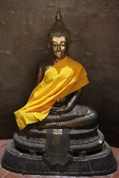 Full size Buddha statue Meditate Which is very old,covered with a yellow robe,the Buddha is made of metal Is durable, stick with gold leaf, very old and is the art of Thailand,take photo at  thailand.