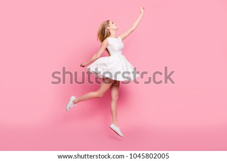 Full-size full-length side view portrait of beautiful attractive carefree tender gentle innocent stylish excited cheerful girl jumping up wants to touch sky isolated on background copy-space