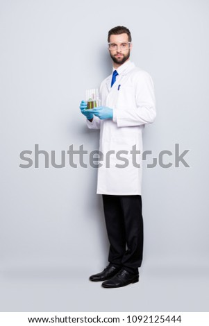 Full size fullbody portrait of attractive stylish scientist in white lab coat, black pants, shoes, tie holding test tubes with multi-colored liquid, looking at camera, isolated on grey background