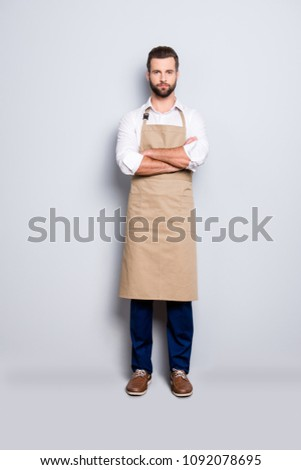Full size fullbody portrait of strict attractive barber in uniform holding arms crossed, looking at camera, isolated over grey background #1092078695