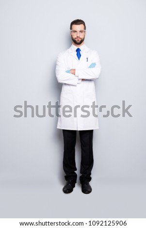 Full size fullbody portrait of stylish handsome scientist with stubble in white outfit with blue tie having his arms crossed looking at camera, isolated on grey background