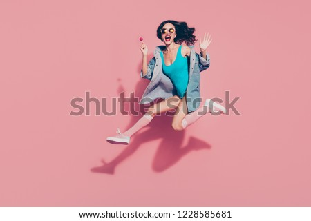 Full size funky positive cheerful attractive lady in style sun spectacles with her stylish trendy wave curly hair she hold sugar sucker on stick isolated on pink background.