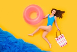 Full size high angle above flat lay view profile photo of beautiful lady seaside resort running hold purse pink float buoy swimming time wear bodysuit isolated yellow color background