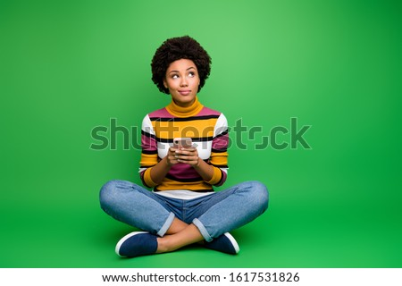 Full size photo minded afro american girl sit legs crossed folded use cell phone blogging think thoughts type social media post wear denim jeans clothes isolated green color background