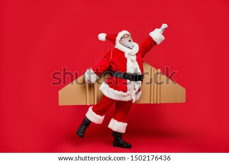 Full size photo of amazed elderly superhero christmas father impressed by fly up turbo speed of his magic imagine rocket wings scream omg wear cap hat isolated over red background