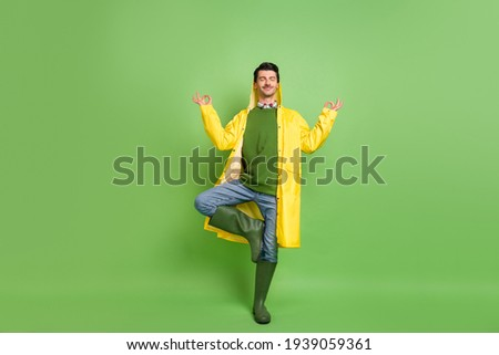 Full size photo of brunet optimistic guy do yoga wear cloak boots isolated on green color background Stock photo ©