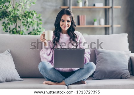 Full size photo of charming happy pretty lady sit couch hold cup look laptop good mood indoors inside house