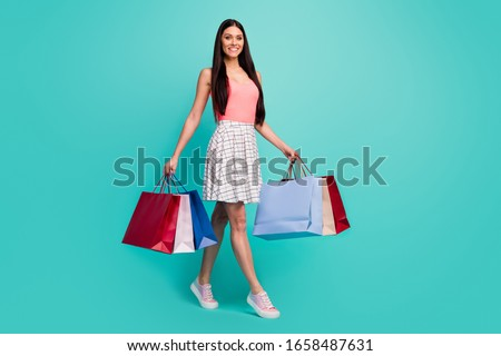 Full size photo of cheerful girl go shopping walk enjoy spring free time bargains hold many bags wear pink singlet footwear isolated pastel turquoise color background