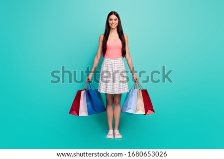 Full size photo of cheerful pretty girl enjoy shopping buy hold many bags wear tank-top shoes isolated over pastel turquoise color background