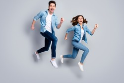Full size photo of cheerful spouses man woman jump run enjoy spring weekend rest relax wear good look clothes footwear isolated over gray color background