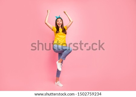 Full size photo of cheerful teen raising her fists screaming wow omg wearing yellow t-shirt isolated over pink background