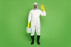 Full size photo of confident guy doctor hold chemical cleaner canister approve covid stop liquid show okay sign wear white latex hazmat uniform breathing mask isolated green color background