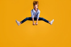 Full size photo of crazy redhead guy jumping high spreading legs sides rejoicing having best free time wear casual trendy outfit isolated yellow background