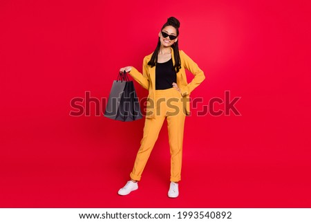 Full size photo of cute lady with bags wear yellow blazer isolated on vivid red color background