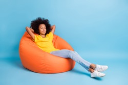 Full size photo of dark skin little brown haired girl sit sleep bean bag isolated on blue color background