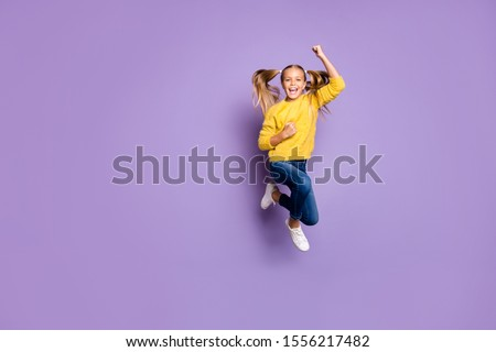 Full size photo of ecstatic child jump win lottery raise fists scream yeah wear casual style clothes isolated over violet color background