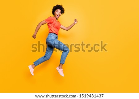 Full size photo of excited amazed girl jump run after sales discounts scream wow omg wear red t-shirt denim jeans sneakers isolated over yellow color background